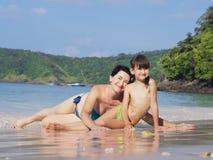 Enfantez et sa petite fille sur la plage image stock