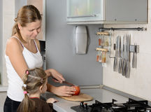 Enfantez et sa pomme de coupe de fille dans la cuisine Images stock