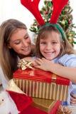 Enfantez et ses cadeaux de Noël de fixation de descendant Images libres de droits