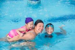 Enfantez et ses enfants heureux dans la piscine Images libres de droits