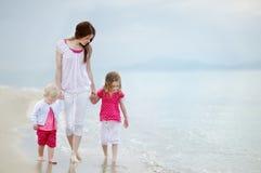 Enfantez et ses enfants marchant le long d'une plage photographie stock libre de droits