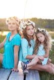 Enfantez et ses filles détendant dehors tout en se reposant sur un chemin en bois dans un domaine au coucher du soleil Image stock