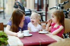 Enfantez et ses filles détendant en café extérieur Photographie stock libre de droits
