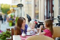 Enfantez et ses filles détendant en café extérieur Image stock