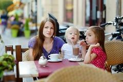 Enfantez et ses filles détendant en café extérieur Photo stock