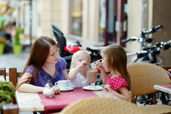 Enfantez et ses filles détendant en café extérieur Image libre de droits