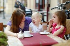 Enfantez et ses filles détendant en café extérieur Photos libres de droits