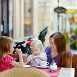Enfantez et ses filles détendant en café extérieur Photographie stock