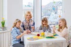 Enfantez et ses filles peignant et décorant des oeufs de pâques Images libres de droits