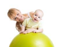 Enfantez et son bébé ayant l'amusement avec la boule gymnastique Image libre de droits