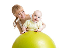 Enfantez et son bébé ayant l'amusement avec la boule gymnastique Image stock