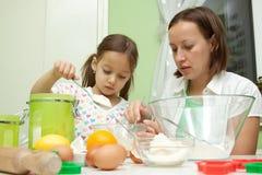 Enfantez et son descendant, faisant cuire au four dans la cuisine Photos libres de droits