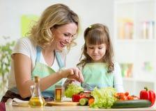 Enfantez et son enfant préparant et goûtant en bonne santé Image libre de droits