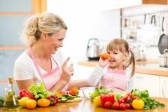 Enfantez et son enfant préparant la nourriture et ayant l'amusement Image libre de droits