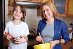 Enfantez et son fils faisant cuire dans la cuisine Images stock