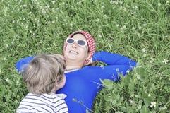 Enfantez et son fils se trouvant sur l'herbe au printemps images stock