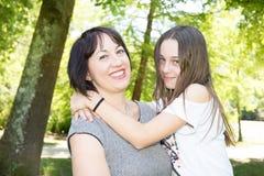 Enfantez et son joli adolescent de fille souriant et posant en parc de jardin photographie stock