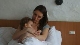 Enfantez et son petit bébé garçon dans le lit dans la chambre ensoleillée clips vidéos