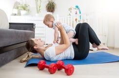Enfantez faire le yoga avec son bébé garçon sur le plancher au salon Image libre de droits
