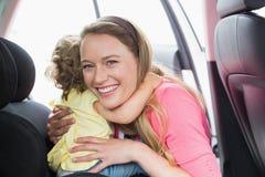 Enfantez fixer son bébé dans le siège de voiture Image stock