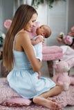 Enfantez jouer avec le bébé nouveau-né s'asseyant sur le plancher Image libre de droits