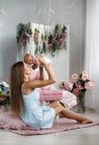 Enfantez jouer avec le bébé nouveau-né s'asseyant sur le plancher Photo stock