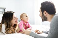 Enfantez l'enfant de père et de bébé sur un lit blanc Photos libres de droits