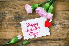 Enfantez la carte de jour du ` s, les oeillets roses et la note Photographie stock