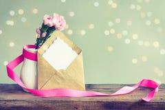 Enfantez la carte de jour du ` s, oeillets roses dans le vase avec le ruban Photos stock