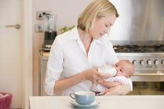 Enfantez la chéri alimentante dans la cuisine avec du café Image libre de droits