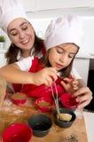 Enfantez la cuisson avec la petite fille dans le tablier et faites cuire les petits pains de moule de remplissage de chapeau avec Image libre de droits