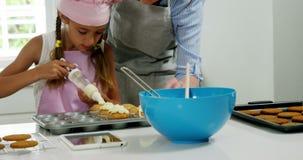 Enfantez la fille de aide pour décorer le petit gâteau avec de la crème banque de vidéos