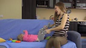 Enfantez la fille de bébé de chatouillement et d'étreinte sur le sofa bleu à la maison clips vidéos