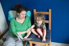 Enfantez la lecture avec son fils à la maison, occasionnel, Photographie stock libre de droits