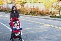 Enfantez la marche avec le fils handicapé dans la poussette o Photos libres de droits