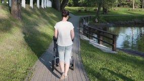 Enfantez la marche avec la voiture d'enfant près du lac, faisant attention banque de vidéos