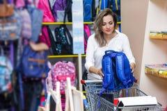 Enfantez la papeterie blanche bleue heureuse de supermarché d'achats de troley de jeune femme de mail de sac d'école d'achat photo libre de droits