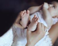 Enfantez la pose avec son petit bébé adorable, tenant ses pieds dans des mains Photographie stock libre de droits