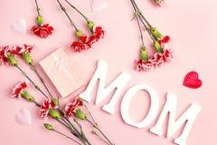 Enfantez le fond de jour du ` s avec les fleurs et le boîte-cadeau d'oeillet sur p Photographie stock