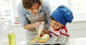 Enfantez le garçon de aide pour décorer le petit gâteau avec de la crème banque de vidéos