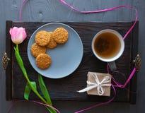 Enfantez le jour du ` s, jour du ` s de femme tulipes, présents, thé et bonbons sur le fond en bois Image stock