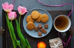 Enfantez le jour du ` s, jour du ` s de femme tulipes, présents, thé et bonbons sur le fond en bois Images libres de droits