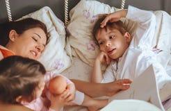 Enfantez le livre de lecture à ses fils dans le lit photographie stock libre de droits
