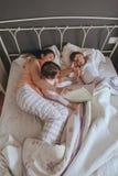 Enfantez le livre de lecture à ses fils dans le lit photo stock
