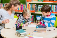 Enfantez le livre de lecture de la bibliothèque à son fils photographie stock