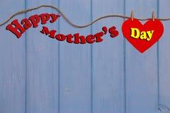 Enfantez le message de jour du ` s avec le coeur de papier rouge et la corde sur le fond en bois bleu Photos stock