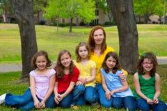 Enfantez le professeur avec des élèves de fille en parc de terrain de jeu image libre de droits