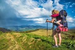 Enfantez le randonneur avec son bébé dans un transport pour un enfant sur le trekking Images libres de droits