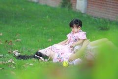 Enfantez les jeux de jeu avec son petit bébé sur la pelouse Image libre de droits