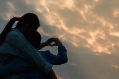 Enfantez les mains et le fils en forme de coeur par lesquels la lumière brille Il image libre de droits